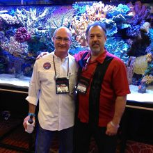 Phillip Moon and Jerry Acuff pose for a picture together in front of a new aquarium.