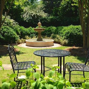 A water fountain behind chairs and a table in a back yard.