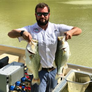 Kyle Moon holds up two beautiful largemouth bass.