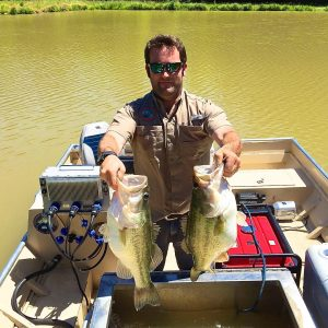 Kyle Moon in the electrofishing boat holds up two huge largemouth bass.