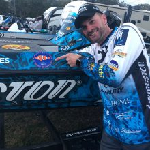 Professional Bass fisherman Randy Howell poses for a picture with his bass boat that has the Alabama Aquarium Logo.