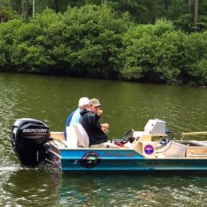 Kyle Moon and a client in the Alabama Aquarium electrofishing boat in a lake.