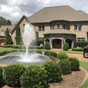 An architectural fountain and spray ring in front of a large custom home.