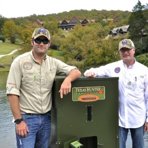 Kyle Moon and Phillip Moon standing next to a Texas Hunter fish feeder beside a lake at Big Cedar Lodge.