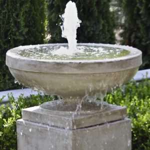 A picture of a stone water fountain pouring water from a large bowl.